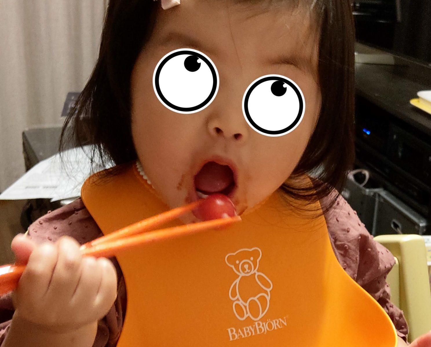 はしでミニトマトを食べる1歳児